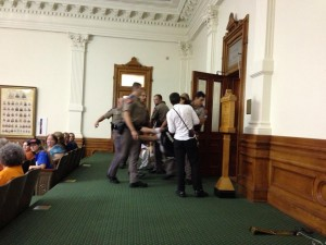 A protestor is forcibly removed from the gallery during HB2 proceedings. Photo by Melissa Conway, provided by Texas Right to Life.