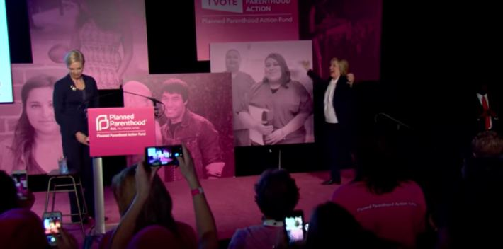 Hillary CLinton raises arms after Planned Parenthood endorsement