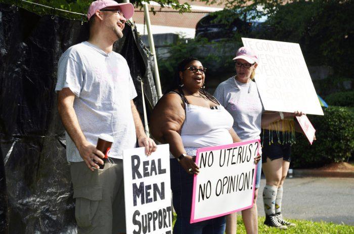 "Jenevieve Hatch holds ""no uterus, no opinion"" sign"