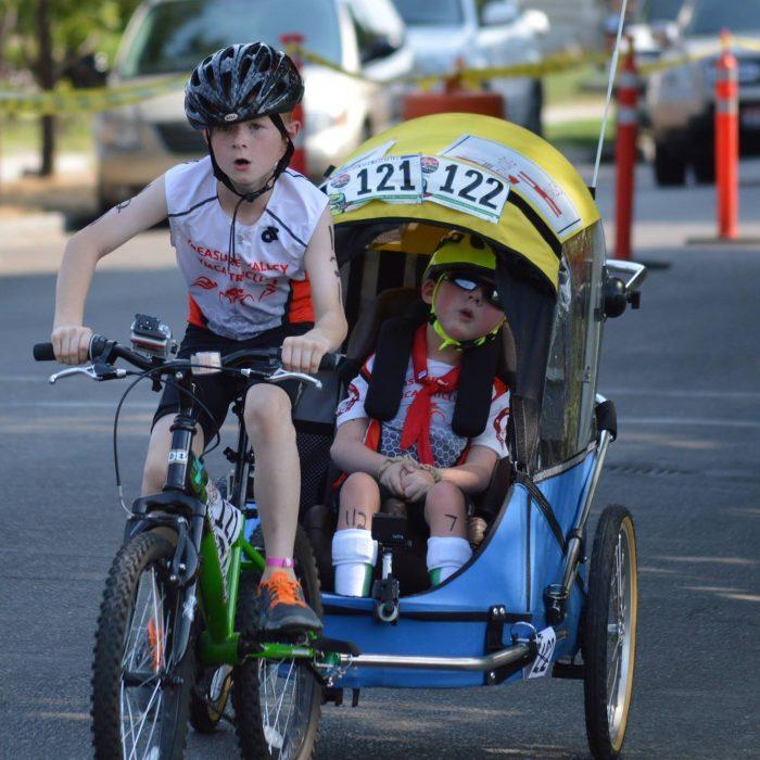 Noah and Lucas Aldrich compete on bike in a triathlon