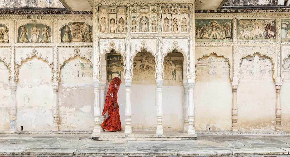 Woman in sari walking through cloister, Pushkar, Rajasthan, India