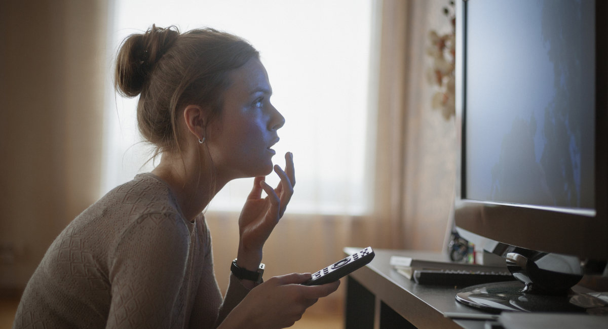 young woman looking in suspense at tv