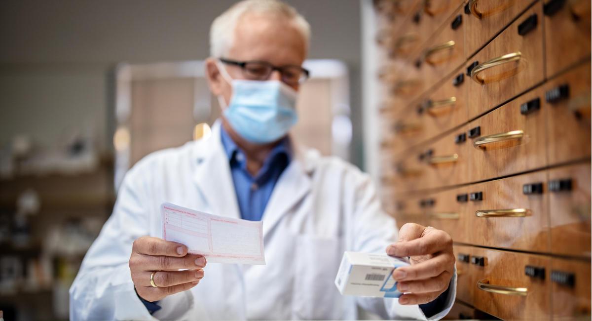 Senior pharmacy worker looking for the medicines in storage rack